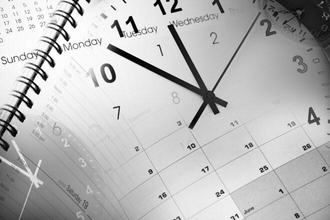 transparente Uhr im Vordergrund eines Terminkalenders